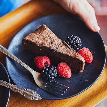 Un morceau de gâteau choco-noisettes dans une petite assiette noire avec trois framboises et deux mûres.