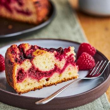Un morceau de gâteau aux framboises et aux betteraves avec trois framboises dans une assiette.