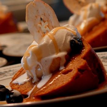 Un morceau de gâteau de patates douces dans une assiette avec une boule de crème glacée sur le dessus.