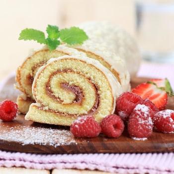 Un gâteau roulé à la confiture avec quelques framboises et fraises.