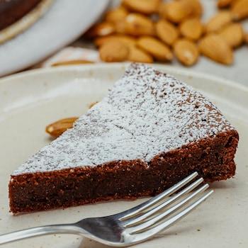 Une pointe de gâteau aux amandes et au chocolat saupoudrée de sucre à glacer.