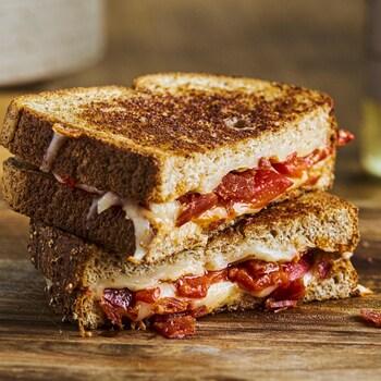 Grilled cheese au chorizo et aux poivrons grillés coupé en deux et posé sur une planche de bois.