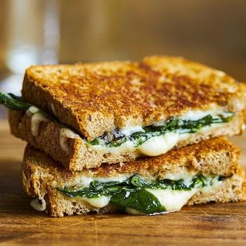 Grilled cheese aux oignons confits et aux épinards coupé en deux et posé sur un comptoir de bois.