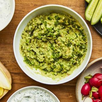 Un petit bol blanc avec de la guacamole avec d'autres bols autour avec des légumes coupés prêts pour la trempette.