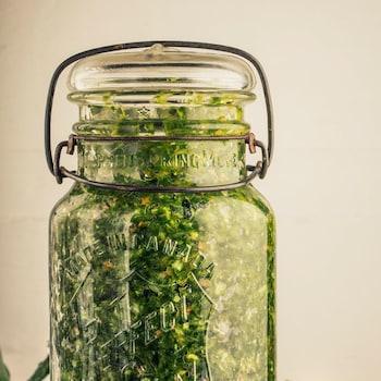 Un pot de verre rempli d'herbes salées.