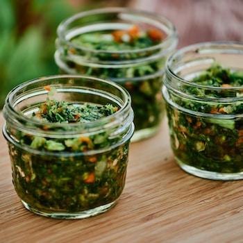 Trois petits pots en verre avec des herbes salées à l'intérieur.