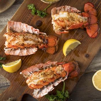 Trois queues de homard sur une planche à découper avec du citron et du persil.