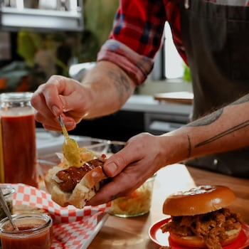 En cuisine, une personne qui garnit un hot-dog au seitan avec des condiments : moutarde, ketchup, relish.