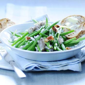 Un bol rempli de salade d'haricots verts, d'huîtres et de pacanes avec une tranche de pain beurrée.
