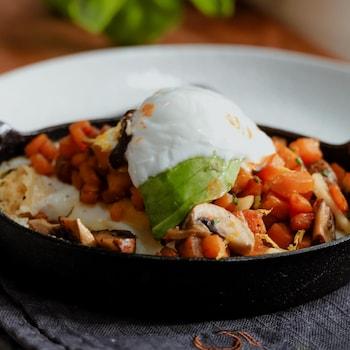 Un hummus déjeuner servi dans une poêle en fonte, garni d'oeufs et de légumes.