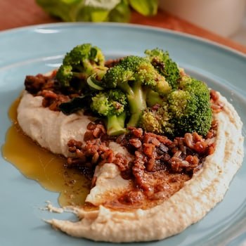 Une assiette contenant du hummus garni de brocolis et de lentilles, le tout nappé de beurre parfumé.