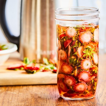 Un grand pot en verre avec l'infusion de queues de fraises à l'intérieur.