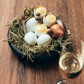 Des coquilles d'oeuf remplie de lait de poule aux champignons, servies dans un bol de céramique sur un lit de paille, aux côtés d'échalotes françaises et de champignons sauvages.