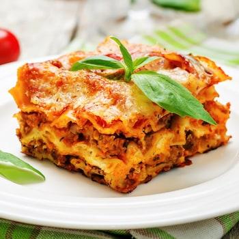 Un morceau de lasagne dans une assiette.