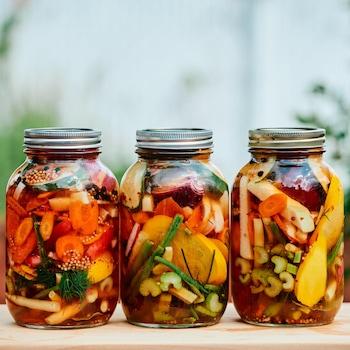 Trois pots masson avec des légumes marinés à l'intérieur.