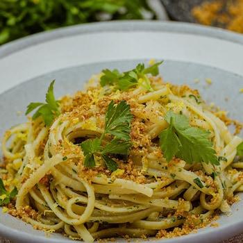 Un bol de linguinis aux oignons confits et aux anchois saupoudrés de chapelure et de persil plat frais.