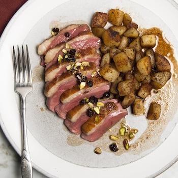 Un magret de canard tranché, servi avec des pommes de terre confites.