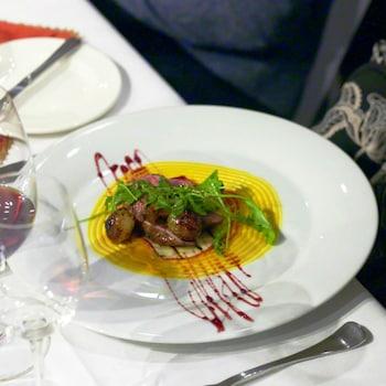 Des morceaux de magret de canard avec des légumes dans une assiette.