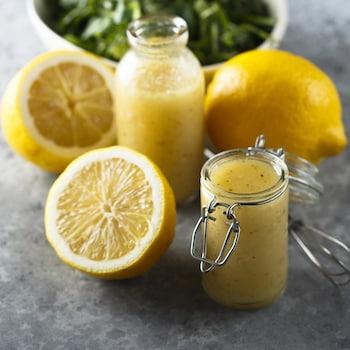 Deux petits pots de marinade au citron entourés de citrons.