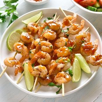 Plusieurs brochettes de crevettes recouvertes de marinade mexicaine.