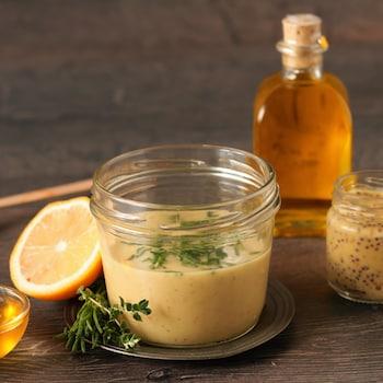 Un pot de marinade miel-moutarde, un pot de moutarde, une bouteille de miel et un morceau de citron.