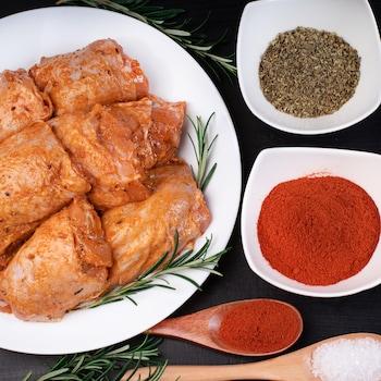 Des morceaux de poulet marinés dans une assiette avec deux bols d'épices.