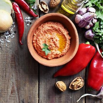 Un bol de marinade au paprika fumé entouré de légumes frais.