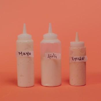 Trois pipettes remplies de mayonnaises différentes: classique, à l'ail (aïoli) et épicée.