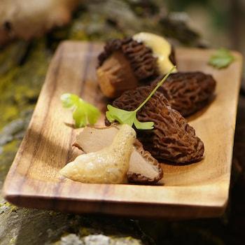 Des morilles, une mousse et du persil sur une assiette en bois.