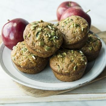Des muffins à la courgette, à la pomme et aux raisins dans une assiette entourée de pommes rouges.