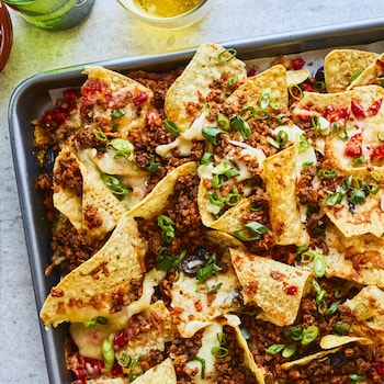 Plaque de nachos garnis de viande, de fromage et d'échalotes vertes.