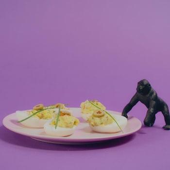 Une assiette d'oeufs mimosa garnis de ciboulette et d'olives.