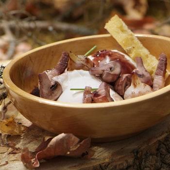 Un œuf poché, des champignons, un croûton de pain et des morceaux de lardons dans un bol en bois.