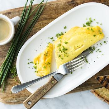 Une assiette blanche avec une omelette française garnie de ciboulette vue de haut et accompagnée de rôties et d'une tasse de café.