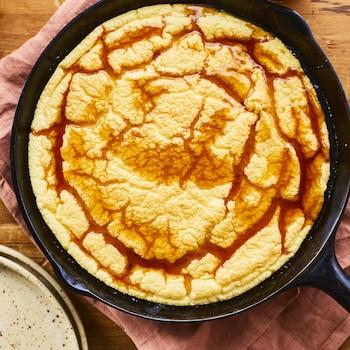 Omelette soufflée garnie de sirop d'érable dans un poêlon en fonte déposé sur un linge de table à coté de deux assiettes empilées.