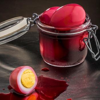 Un pot de verre avec des œufs au vinaigre de betterave rouges.