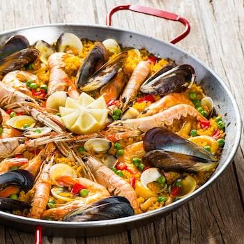 Une paella de langoustes, de moules et de palourdes dans une casserole.