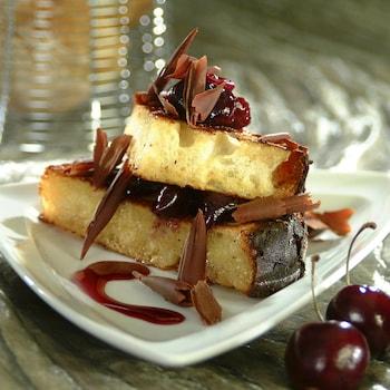 Deux morceaux de pain perdu aux épices l'un sur l'autre avec des copeaux de chocolat et de la confiture de cerise.