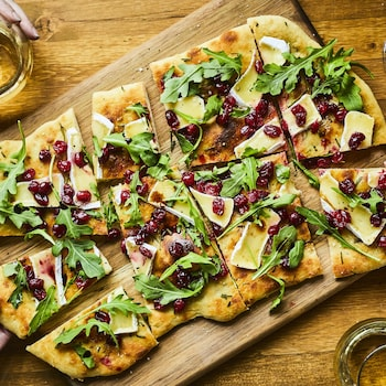 Des mains prennent une portion de pain plat coupé, recouvert de fromage brie, roquette et canneberges.