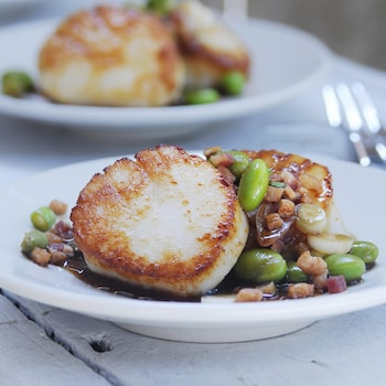 Une assiette avec des pétoncles poêlés et sa vinaigrette.