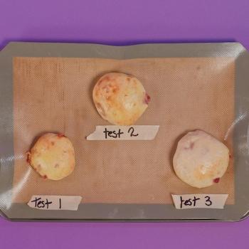 Trois spécimens de pizzas pochettes sur une plaque tapissée de papier de cuisson.