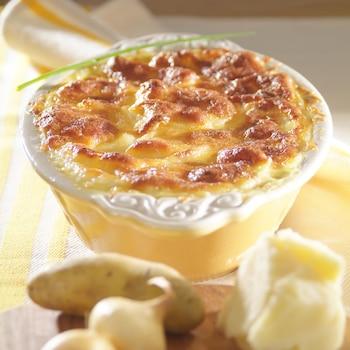 Un petit plat allant au four rempli de pommes de terre gratinées.