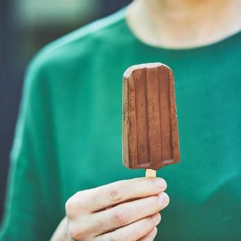 Main qui tient un pops glacé au chocolat.