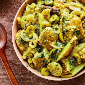 Il est possible de voir un bol contenant le poulet au citron et aux olives à la marocaine au centre de la photo. Il y a une cuillère de bois à la gauche du bol, des assiettes et un linge de table à la droite.