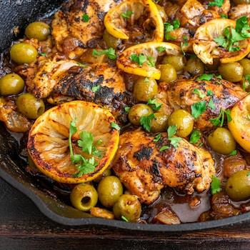 Une poêle remplie de poulet, de citrons et d'olives.