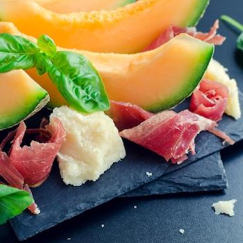 Des morceaux de cantaloup, du parmesan, du prosciutto et du basilic sur une planche à découper.