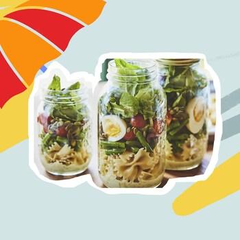 Trois pots de salade niçoise avec un parasol.