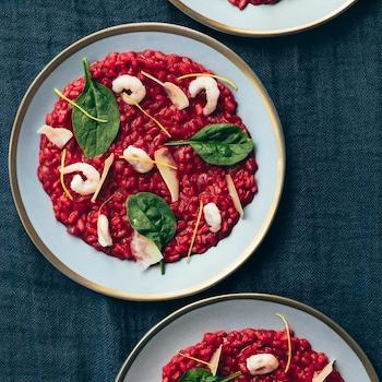 Des assiettes de risotto sanguin avec des crevettes et des épinards.