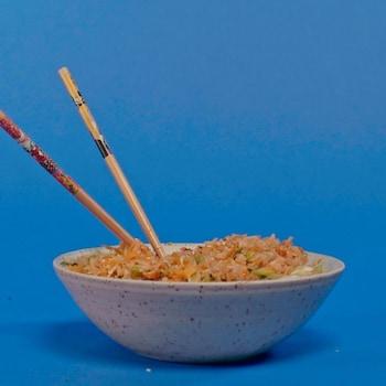 Un bol rempli de riz frit avec baguettes de bois.