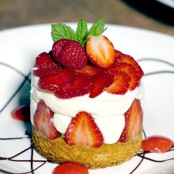 Un sablé breton recouvert de beaucoup de crème chantilly et de fraises.